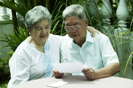 Old couple reading a letter together Stock Photo - 12643197