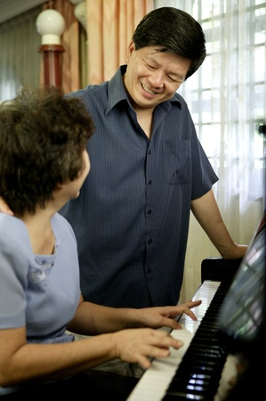 Man watching his wife playing piano Stock Photo - 12643212