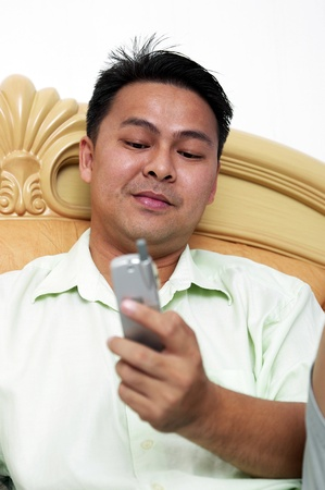 Man sending text messages with his handphone Stock Photo - 12643286