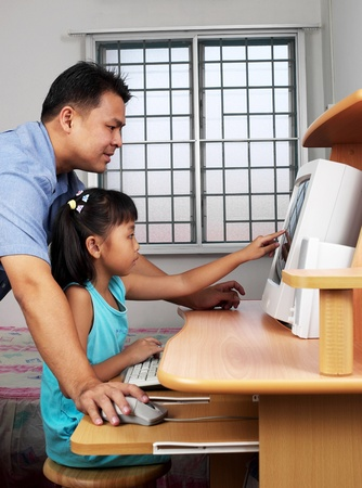 Side shot of man teaching his daughter how to use a computer LANG_EVOIMAGES