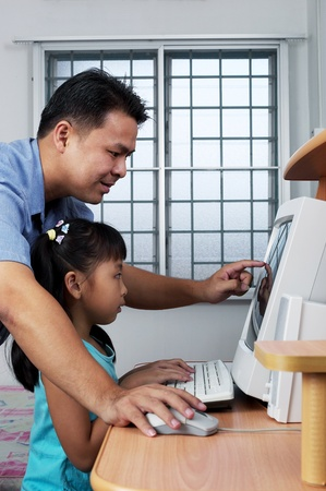 Side shot of man teaching his daughter how to use a computer Stock Photo - 12643302