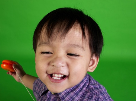 Studio shot of boy in checkered shirt playing with a yo-yo Stock Photo - 12643361