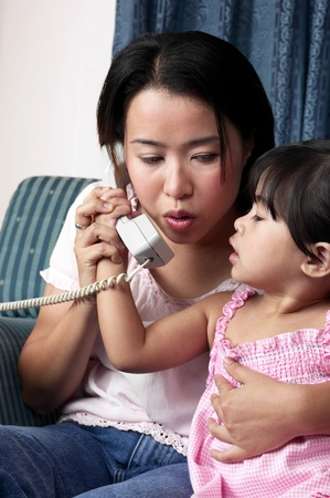 Girl snatching the phone from her mother Stock Photo - 12643415