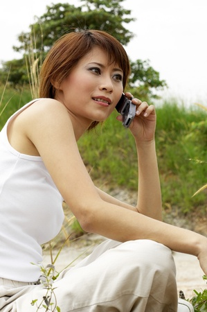 Side shot of woman sitting on a grass field talking on the handphone Stock Photo - 12643521