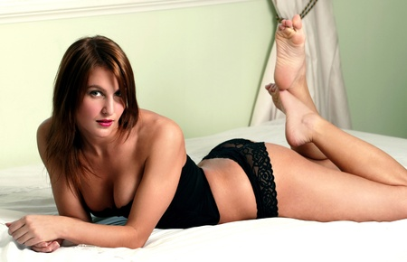 Woman in black lingerie lying forward on the bed with her legs up Stock Photo - 12643576