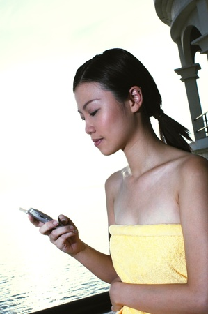 Woman in yellow towel text messaging on her handphone Stock Photo - 12643591