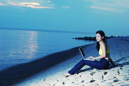 Side shot of woman using laptop on the beach Stock Photo - 12643593