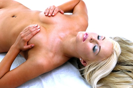 Mujer desnuda durmiendo en la cama con las manos cubriendo sus senos Foto de archivo - 12643637
