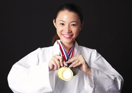 Taekwando practitioner showing off her gold medals Stock Photo - 12643760
