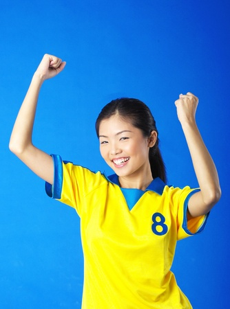 Woman in football jersey jubilating after scoring a goal Stock Photo - 12643798