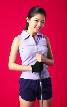 Studio shot of woman posing with a golf club Stock Photo - 12643813