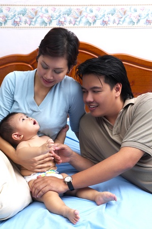 Parents and a baby posing on the bed Stock Photo - 12643866