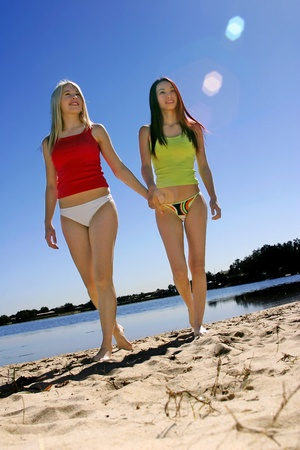 Low angle view of two women taking a stroll along the beach Stock Photo - 12643905