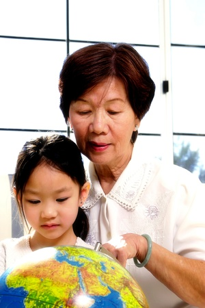 Old woman teaching her granddaughter how to refer to a globe Stock Photo - 12643940