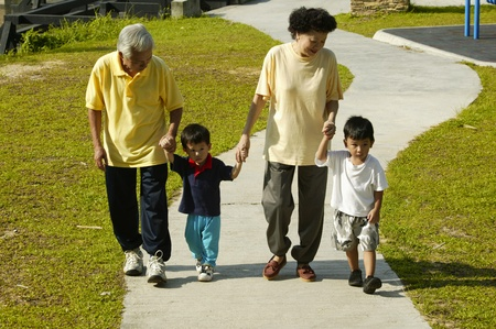 Old couple bringing their grandsons out for a walk in the park Stock Photo - 12644046