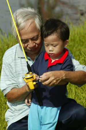 Old man teaching his grandson how to fish Stock Photo - 12644047