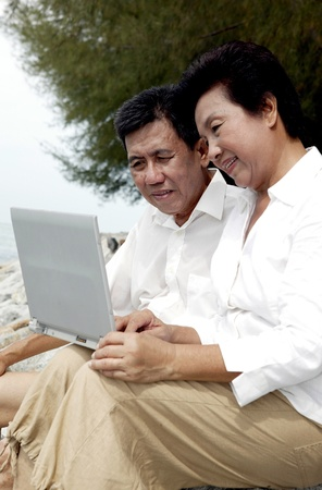 Old couple using laptop while holidaying on the beach Stock Photo - 12644085