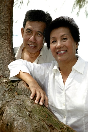 Old couple posing beside a tree Stock Photo - 12644086