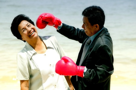 Old man in red boxing gloves jokingly boxing his wife Stock Photo - 12644090