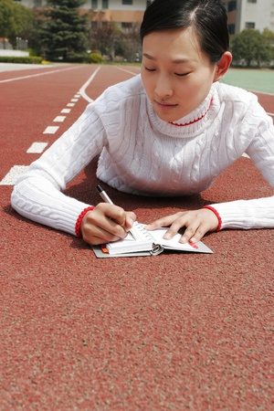 Girl lying forward on the track writing on her organizer. Stock Photo - 12644150