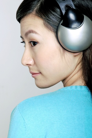 Woman listening to music on the headphones. Stock Photo - 12644184