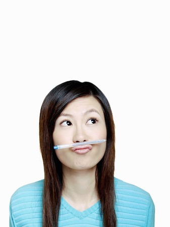 Woman balancing pen between mouth and nose. Stock Photo - 12644210