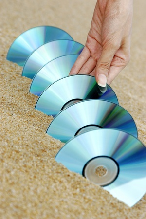 Hand arranging compact discs on the beach. Stock Photo - 12644229