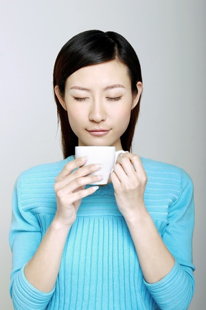 Woman enjoying a cup of aromatic coffee. Stock Photo - 12644298