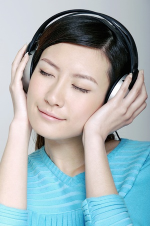 Woman listening to music on the headphones. Stock Photo - 12644304