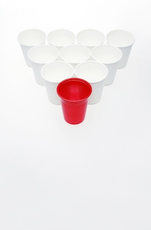 One single red cup among all white cups arranged into a triangle Stock Photo - 12644359
