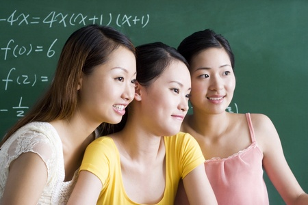 Three beautiful young women posing in the classroom Stock Photo - 12644364