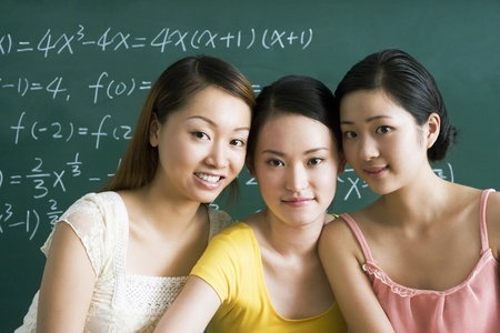 Three beautiful young women posing in the classroom Stock Photo - 12644397