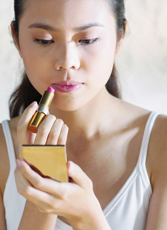 Woman looking at the compact mirror while applying lipstick on her lips Stock Photo - 12644662