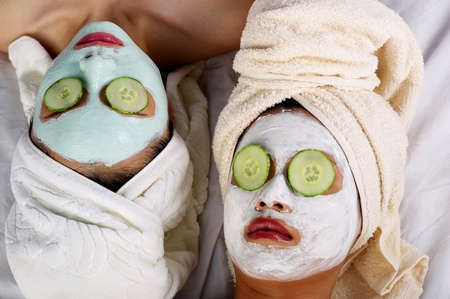 Two women with towel wrapped hair doing facial mask LANG_EVOIMAGES