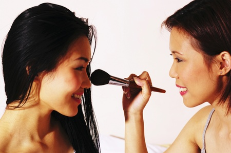 Woman helping her friend to apply some loose powder on her face Stock Photo - 12644706