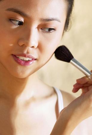 Woman applying some blusher on her cheek Stock Photo - 12644707