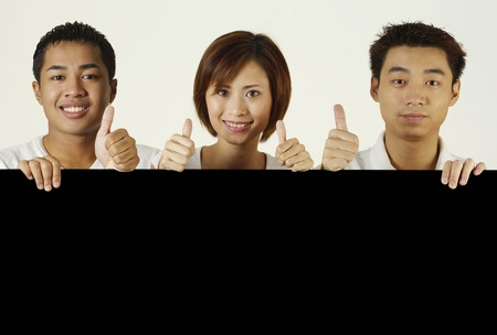 Men and woman holding black board and showing thumbs up Stock Photo - 12644727