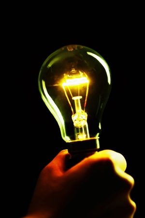 Hand holding a lit lightbulb in a dark place Stock Photo - 12645050