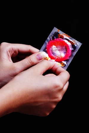 Hands poking a packet of condom with a neeedle Stock Photo - 12645066