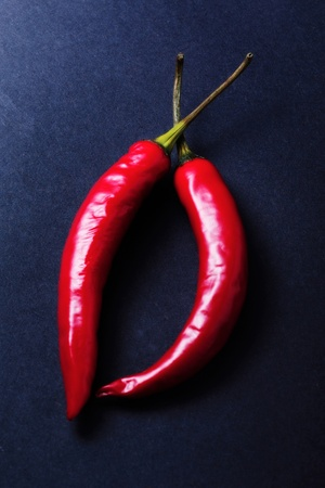Two red chillies on the table Stock Photo - 12645075