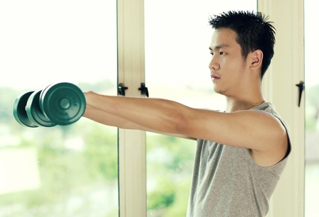 Side shot of a man lifting up two dumbbells Stock Photo - 12645125