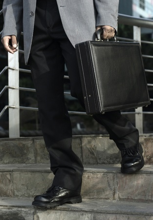 Waist down shot of a businessman carrying briefcase walking down the stairs Stock Photo - 12645184