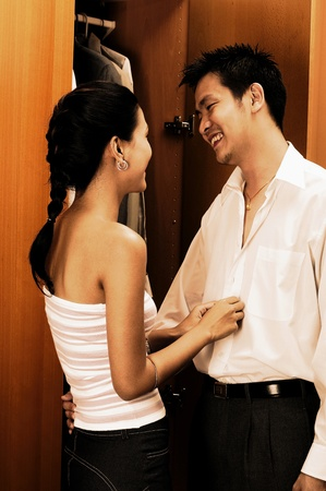 Woman helping her husband to button his shirt Stock Photo - 12645409
