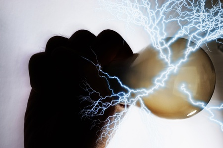 Hand grabbing a lightbulb tightly causing some energy being released from it Stock Photo - 12645439