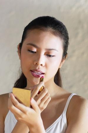 Woman carefully applying lipstick on her lips Stock Photo - 12645446