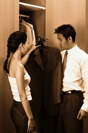 Woman helping her husband to choose coat Stock Photo - 12645521