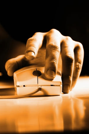 Hand clicking on a computer mouse Stock Photo - 12645523