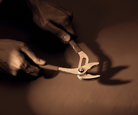 Hand using a plier and its shadow Stock Photo - 12645668