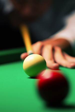 Hand holding cue aiming at a red ball