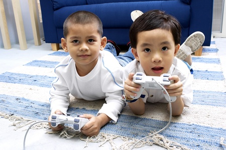 Two boys playing video game console at home Stock Photo - 12645730